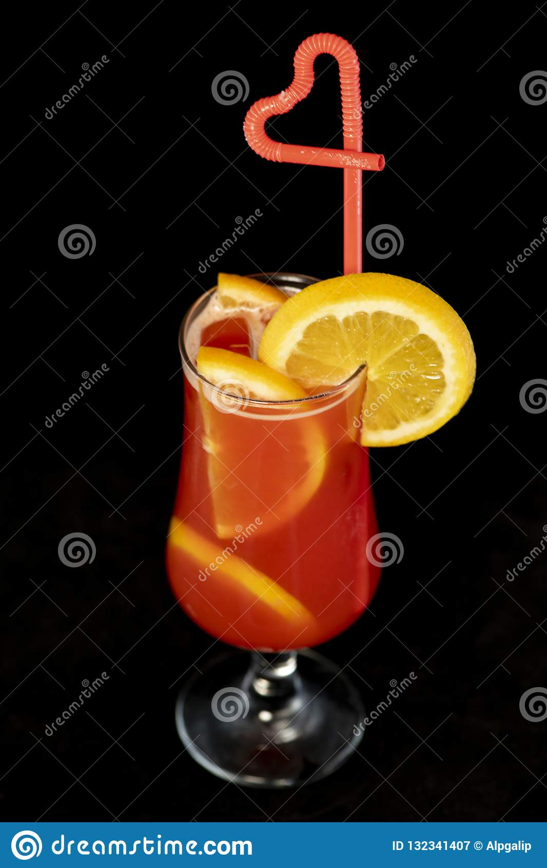 Alcoholic cocktail with lemons inside and lemon wedge on the glass with straw