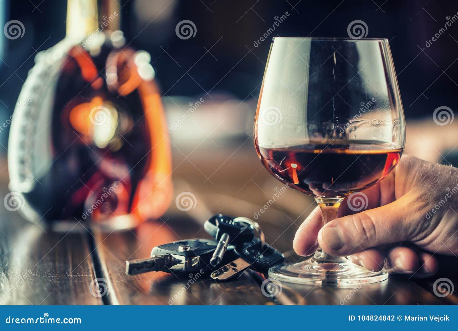 Alcoholism Coloque o homem da mão do conhaque ou da aguardente as chaves ao carro