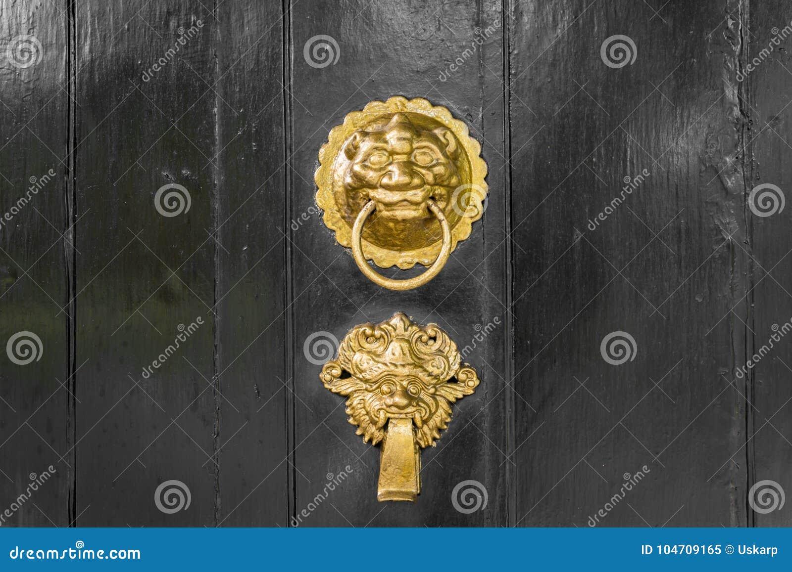 Aldrava de porta antiga do ouro ou do bronze ornamentado
