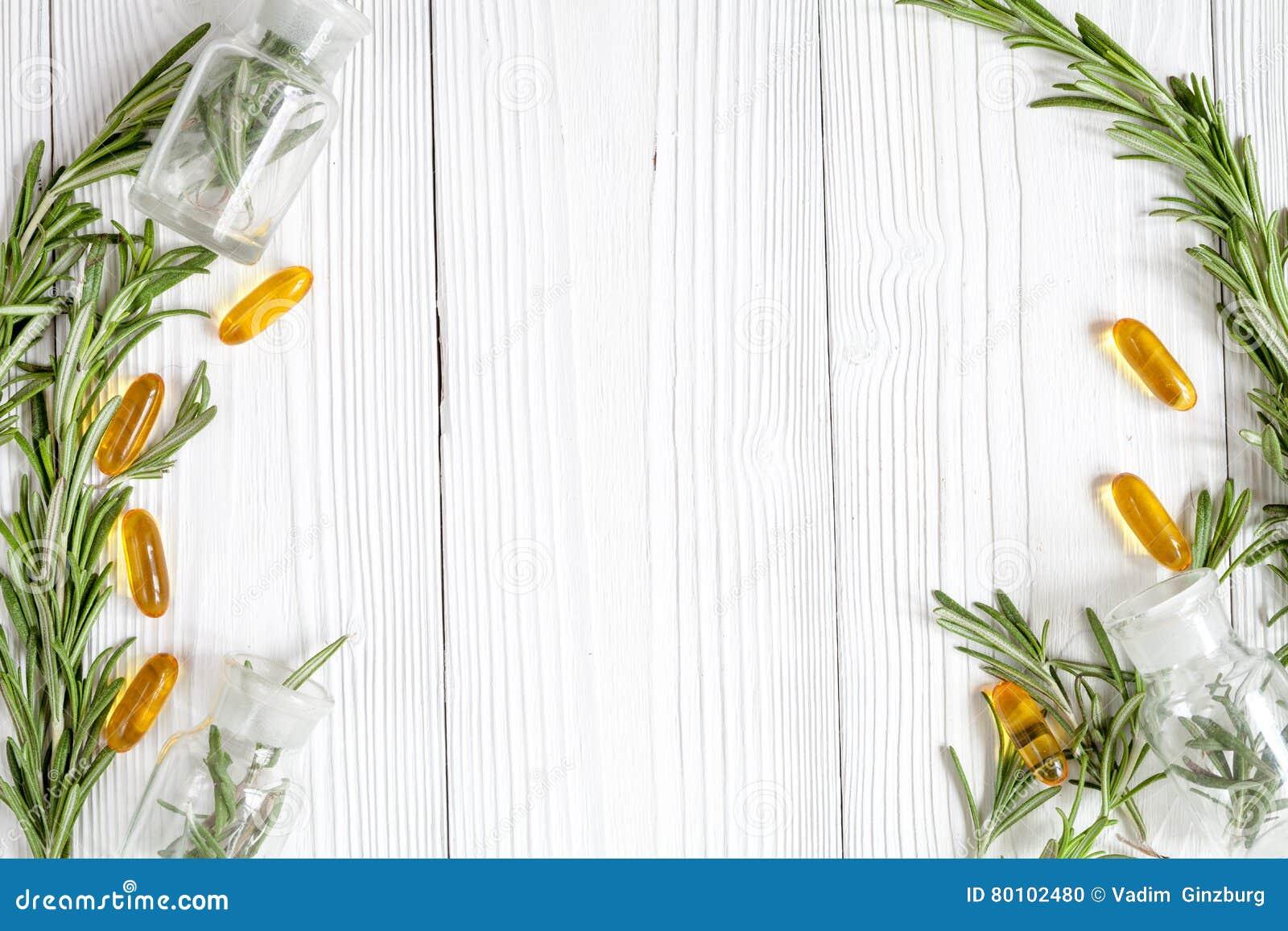 Alecrins frescos com os comprimidos na opinião superior do fundo de madeira