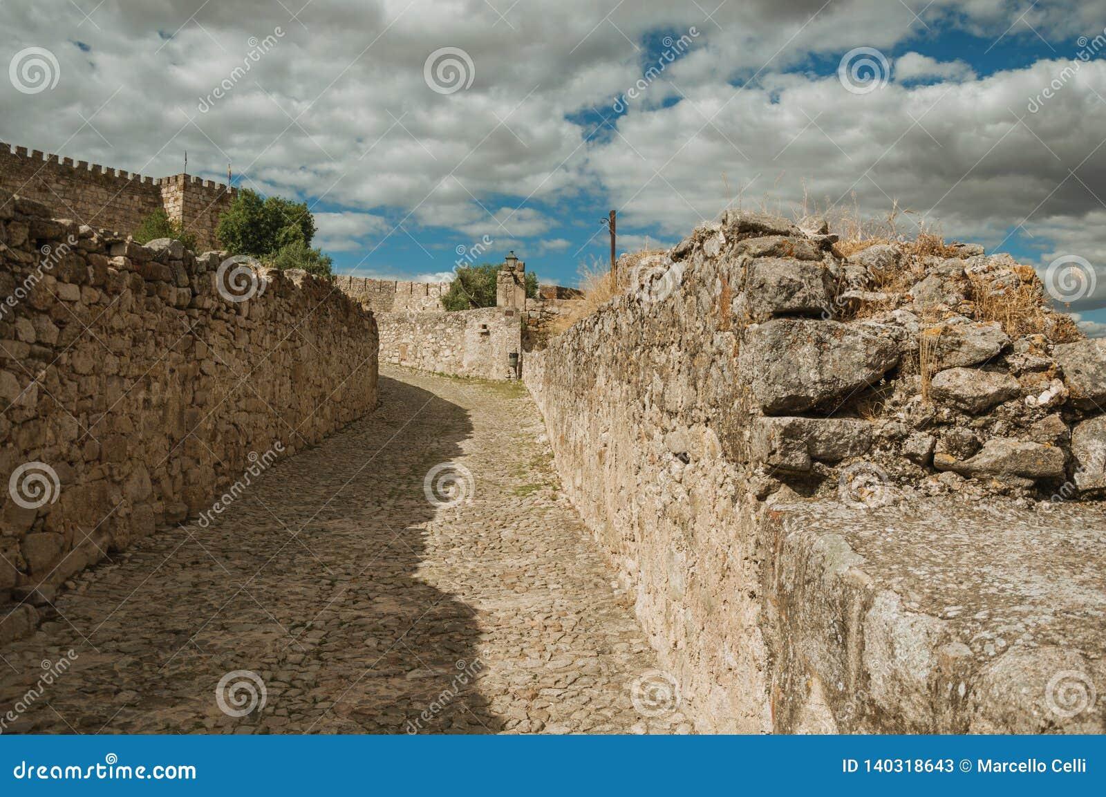 Aleia com as paredes de pedra para o castelo de Trujillo