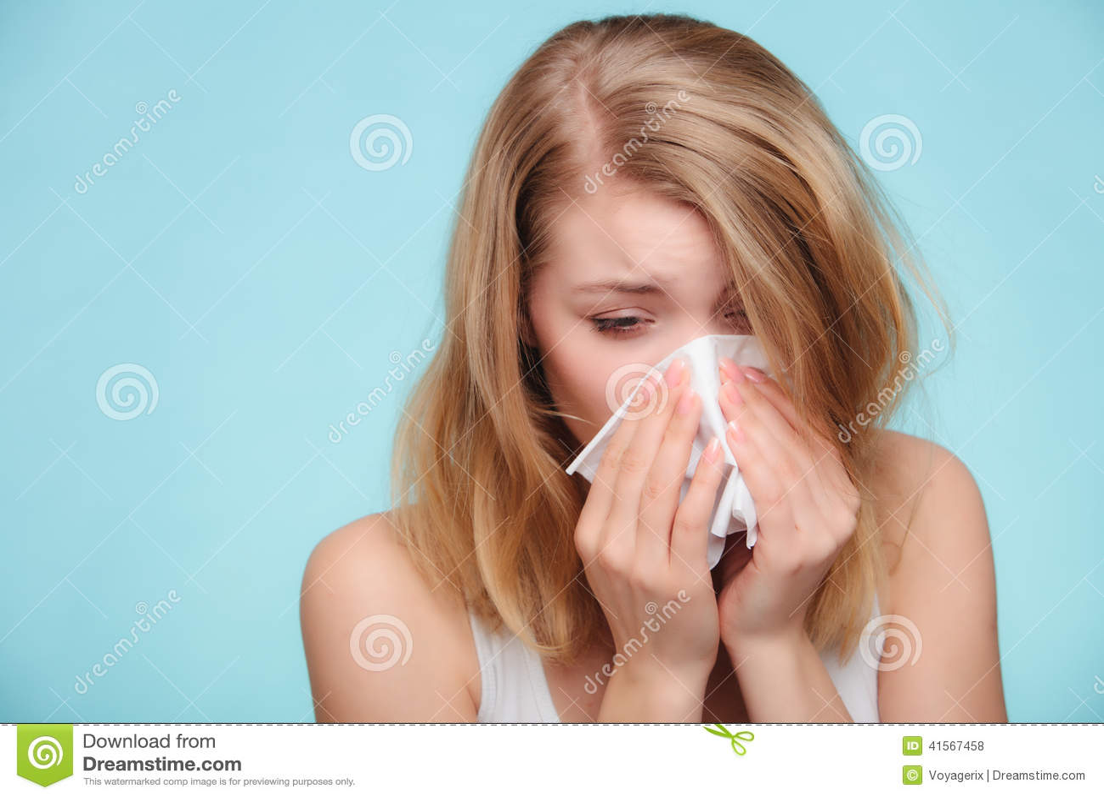 Alergia da gripe Menina doente que espirra no tecido saúde