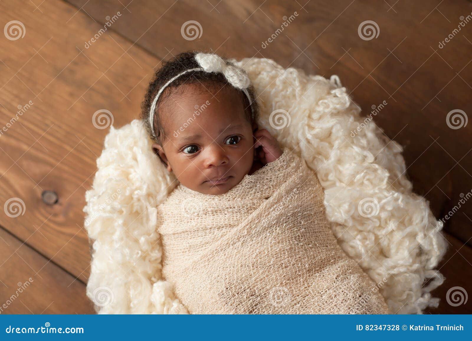Alert Newborn Baby Girl Swaddled in a Stretch Wrap