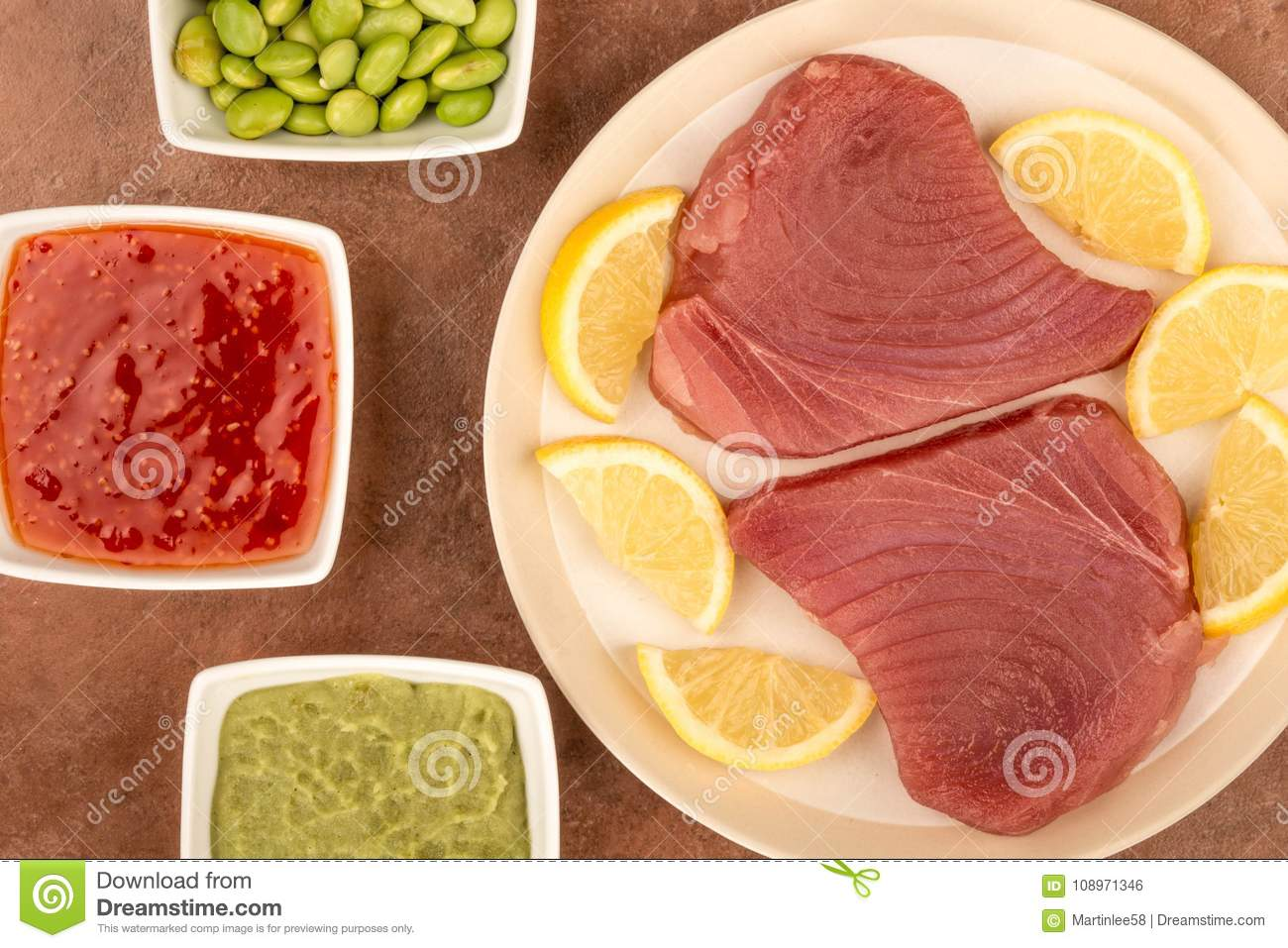 Aleta amarilla cruda cruda fresca Tuna Steaks With Lemon Slices