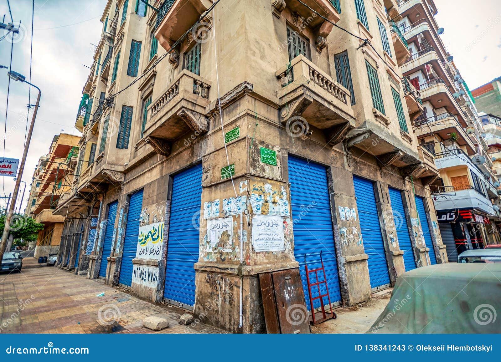 11 16 2018 Alexandría, Egipto, clase de una esquina de una casa vieja con las puertas brillantes y azules inundadas con los anunc