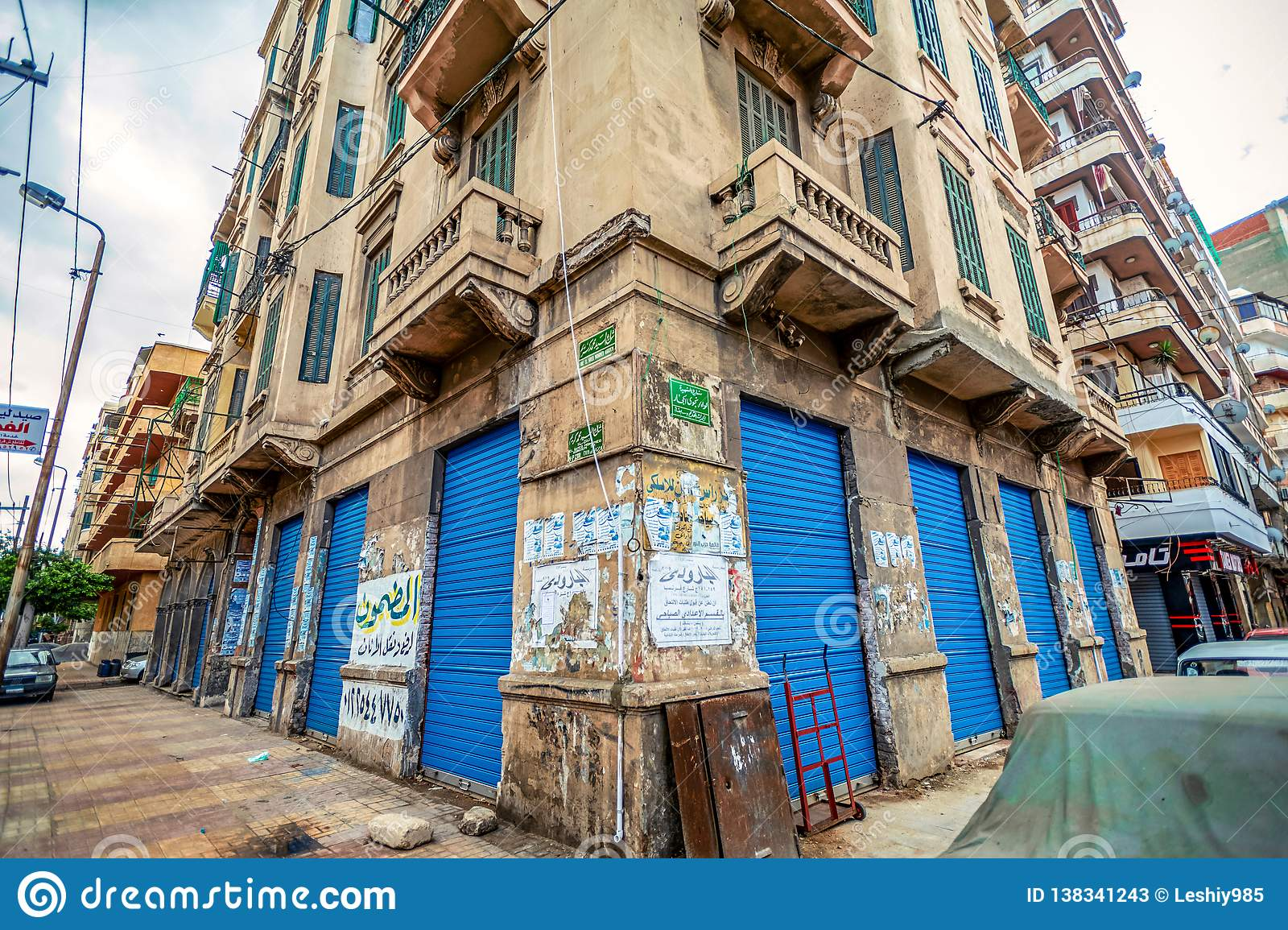 11.16.2018 Alexandria, Egypt, Kind of a corner of an old house with bright and blue doors flooded with old advertisements