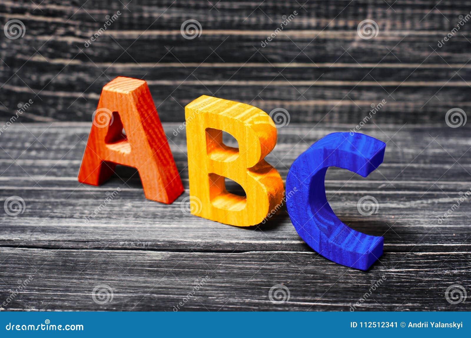Alfabet som göras av trä på bakgrunden av ett bräde, ebenholts Conce