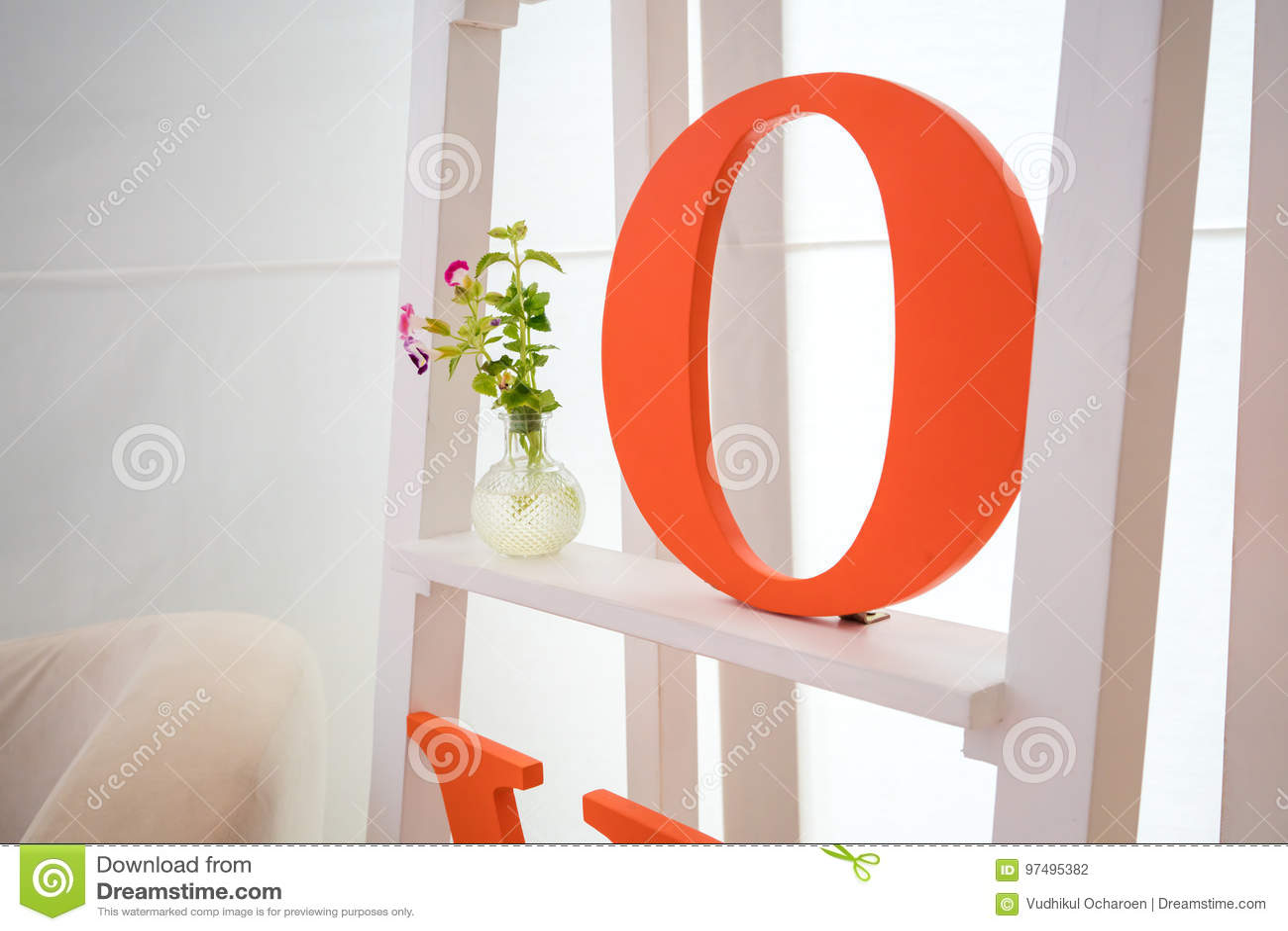 Alfabeto arancio sullo scaffale bianco con il fiore