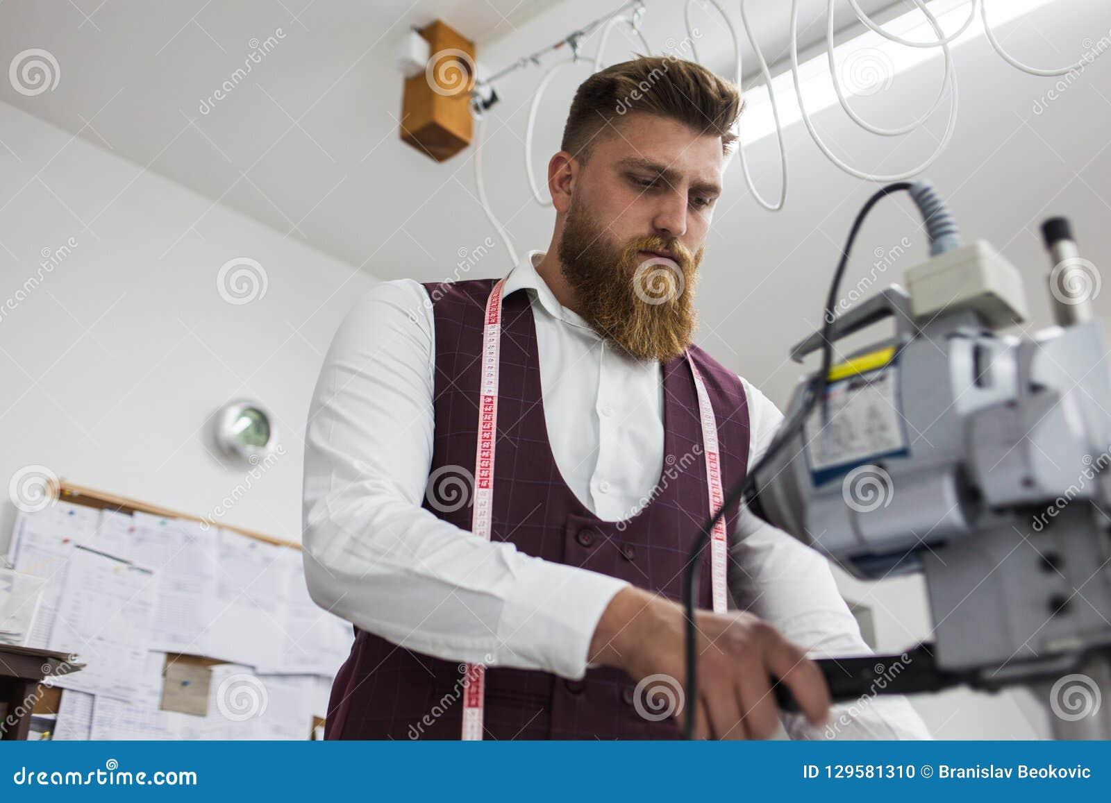 Alfaiate novo da barba que trabalha no projeto novo da roupa