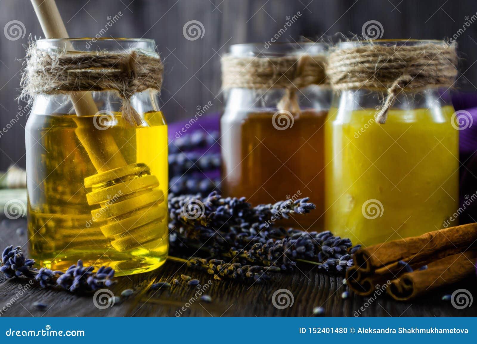 Alfazema e mel erval nos frascos de vidro com a colher do mel no fundo de madeira escuro