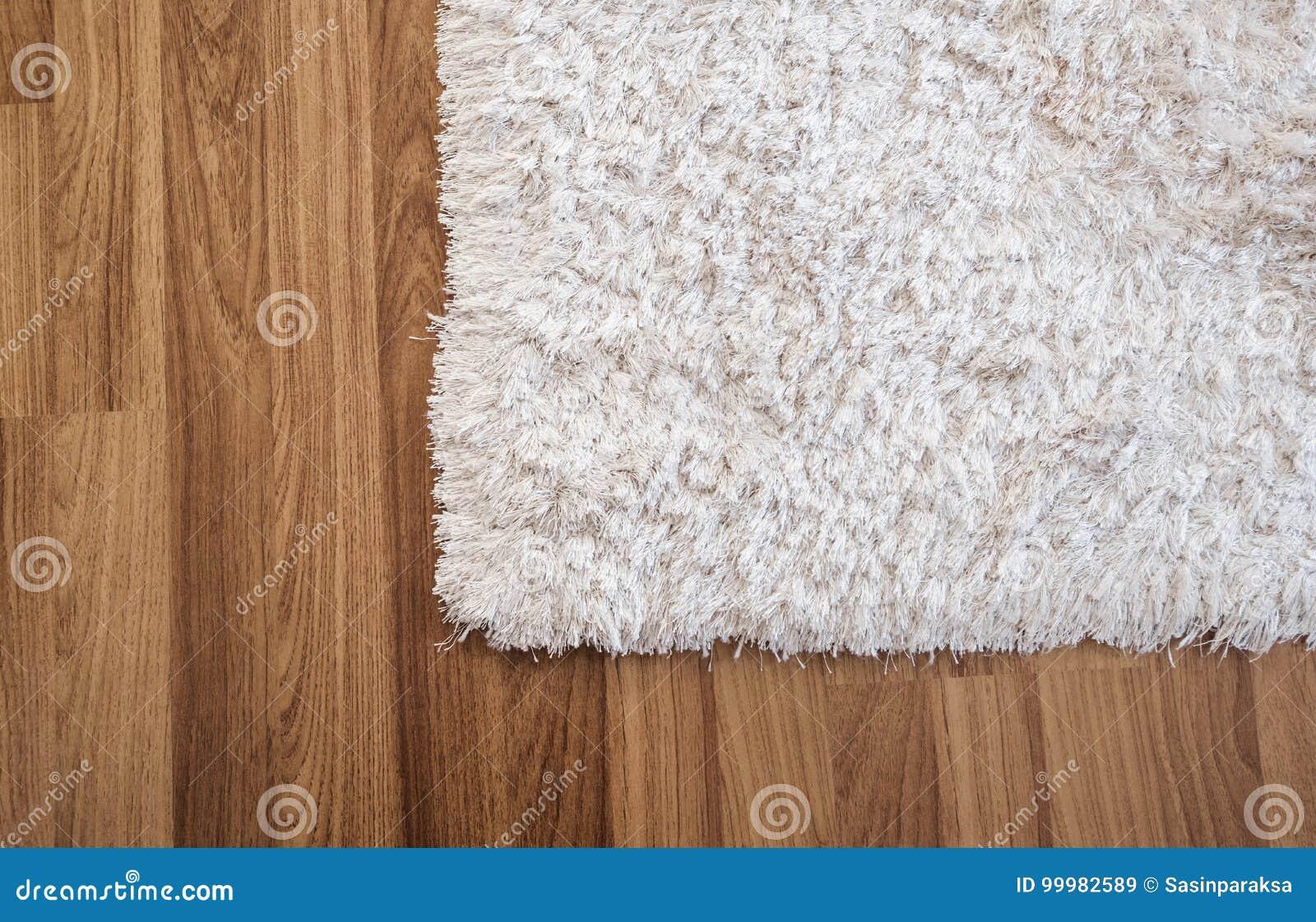 Alfombra blanca del primer en piso de madera laminado en la sala de estar, decoración interior