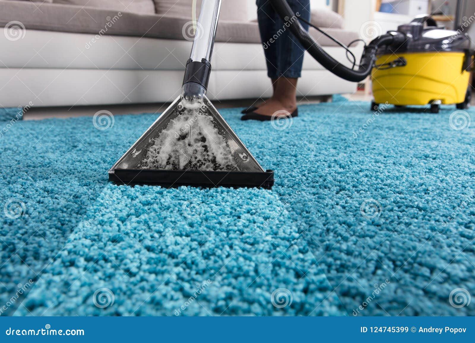 Alfombra de la limpieza de Person Using Vacuum Cleaner For