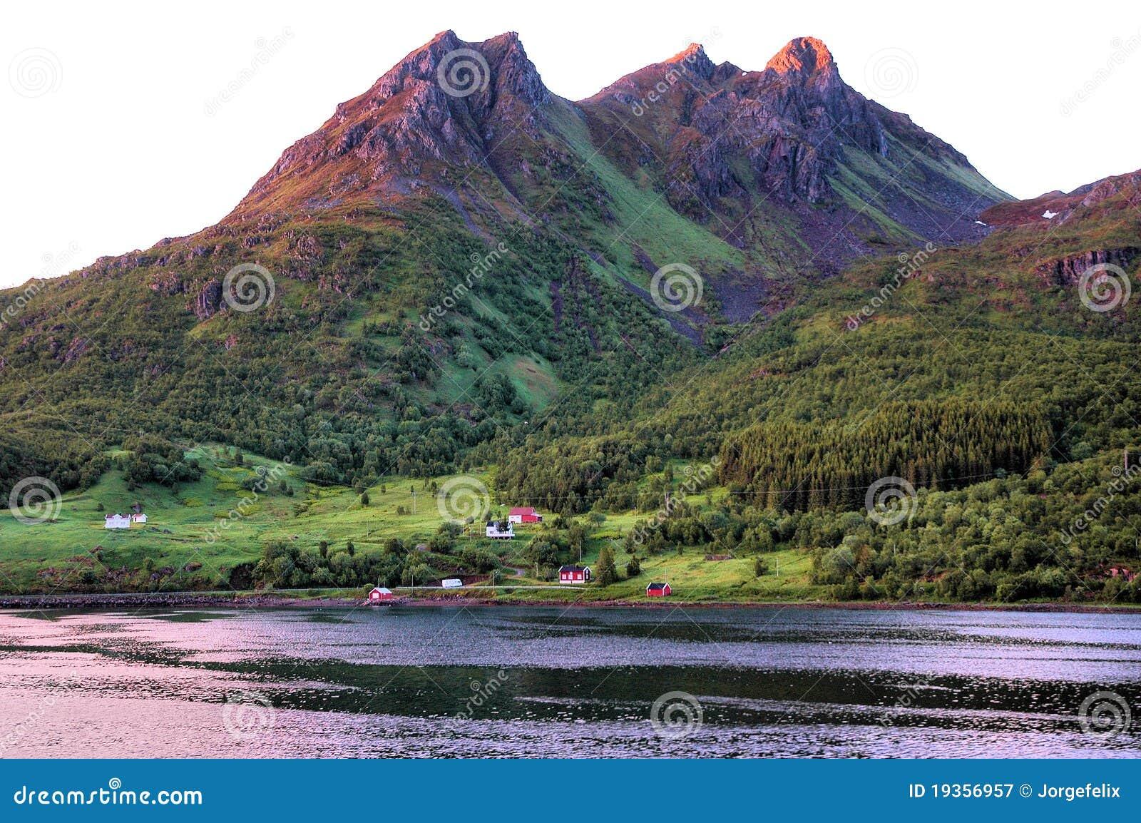 Algumas casas na costa montanhosa de um Norwegia
