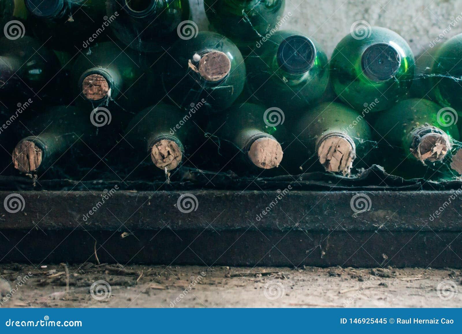 Algunas botellas de vino muy viejas y polvorientas en una bodega