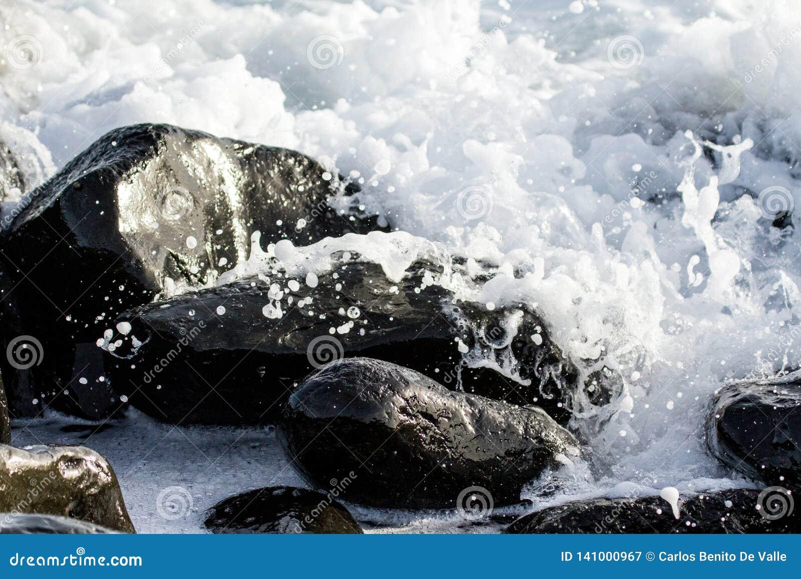 Algunas piedras negras debajo de las ondas