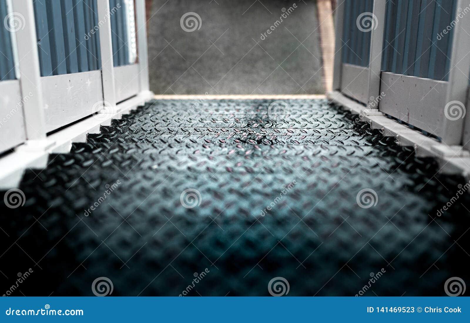 Algunos pasos mojados peligrosos del metal con una verja de madera blanca