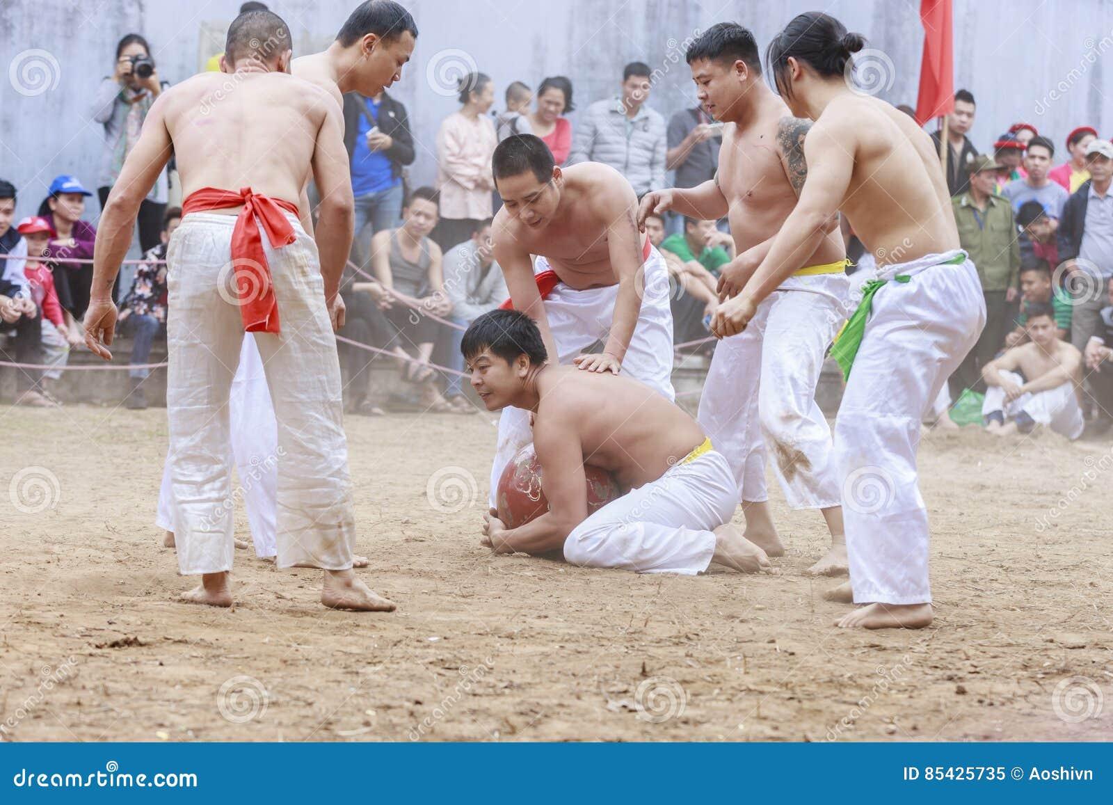 Alguns homens novos jogam com a bola de madeira no ano novo lunar do festival em Hanoi, Vietname o 27 de janeiro de 2016