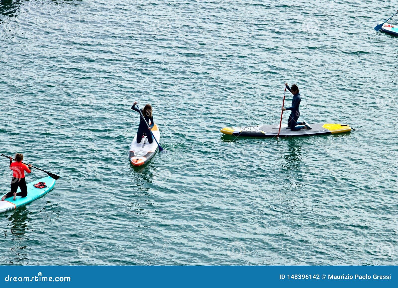 Alguns meninos e meninas remam em uma placa na superf?cie do mar Vista de acima