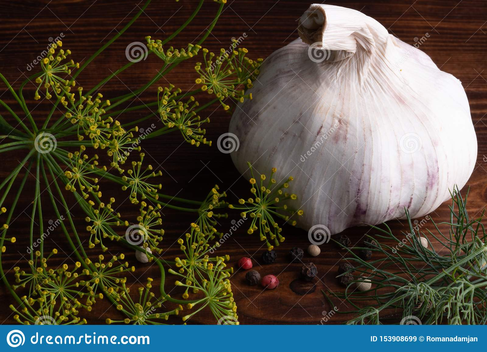 Alho enorme, rústico com pimenta preta, branca, vermelha, aneto e salsa na tabela de madeira velha Baixa chave