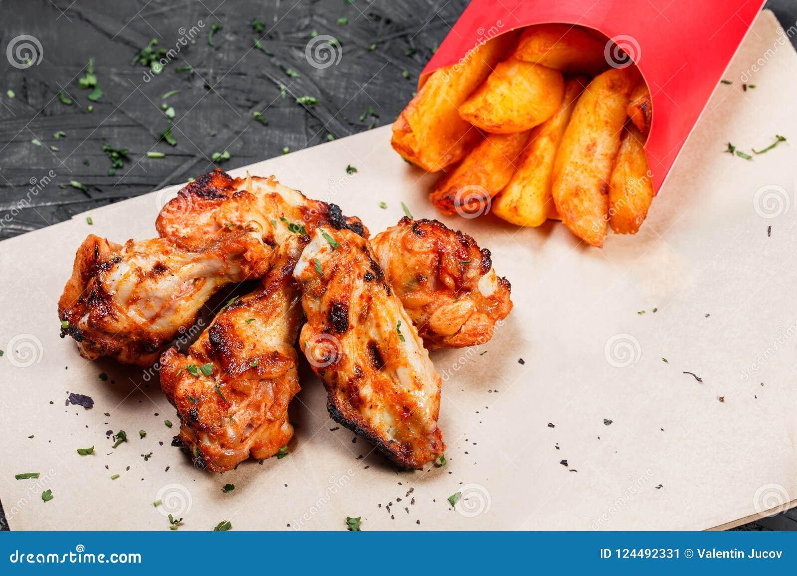 Ali di pollo fritto con le patate al forno sulla carta del mestiere su fondo nero