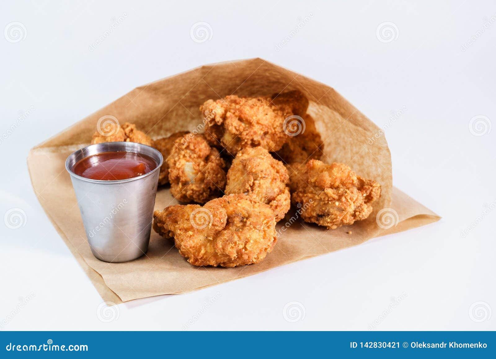Ali di pollo fritto con salsa al pomodoro su un fondo bianco