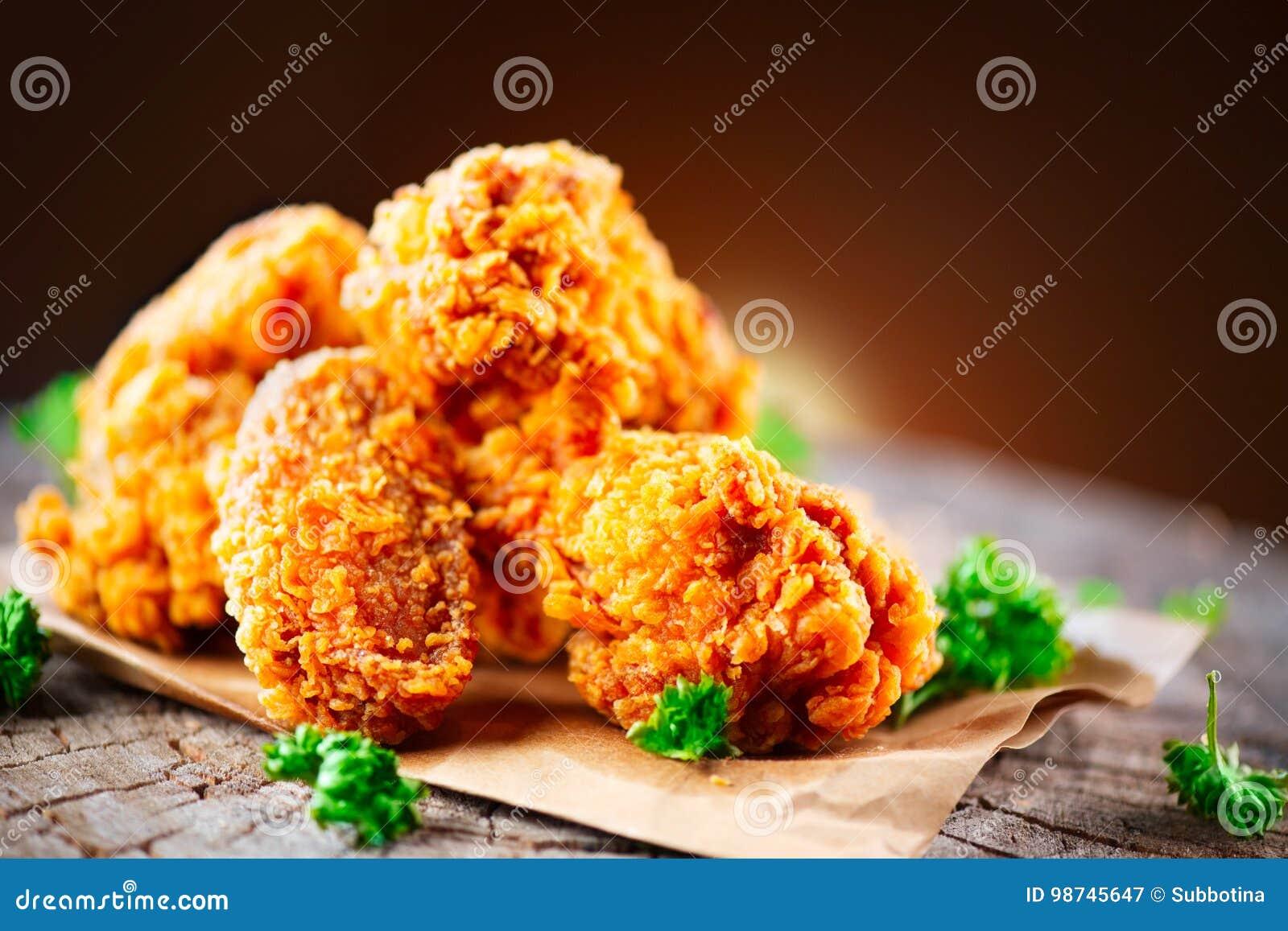 Ali e gambe di pollo fritto sulla tavola di legno