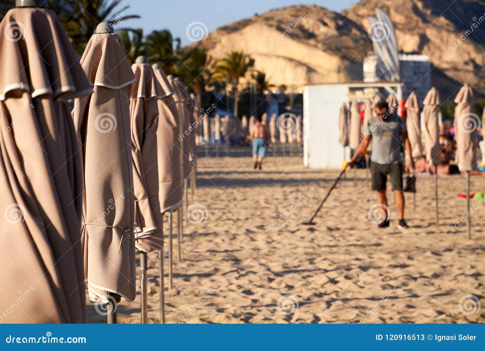 ALIACNTE SPANIEN, CIRCA JULI 2018 män med en metalldetektor på stranden