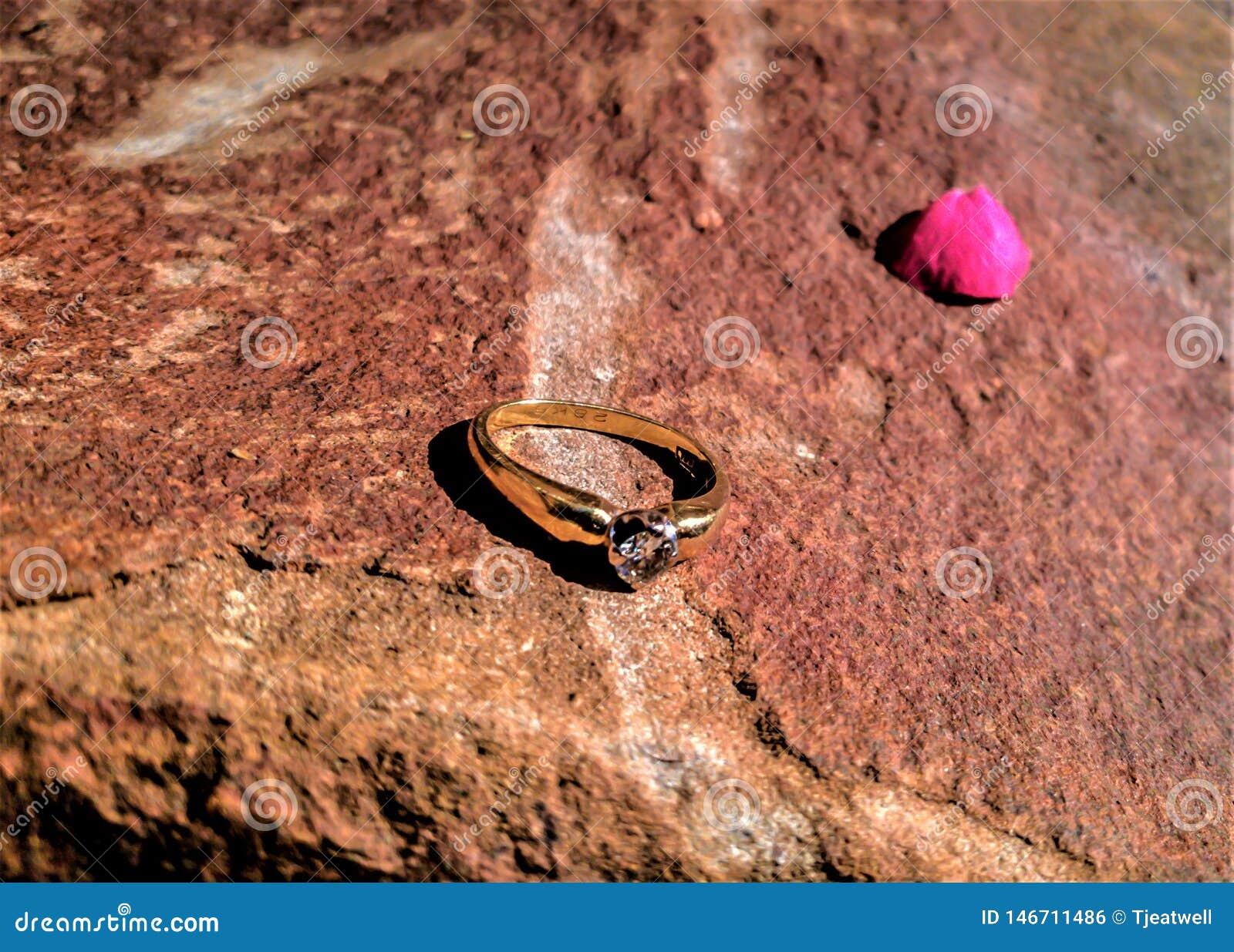 Aliança de casamento do ouro em uma superfície da rocha