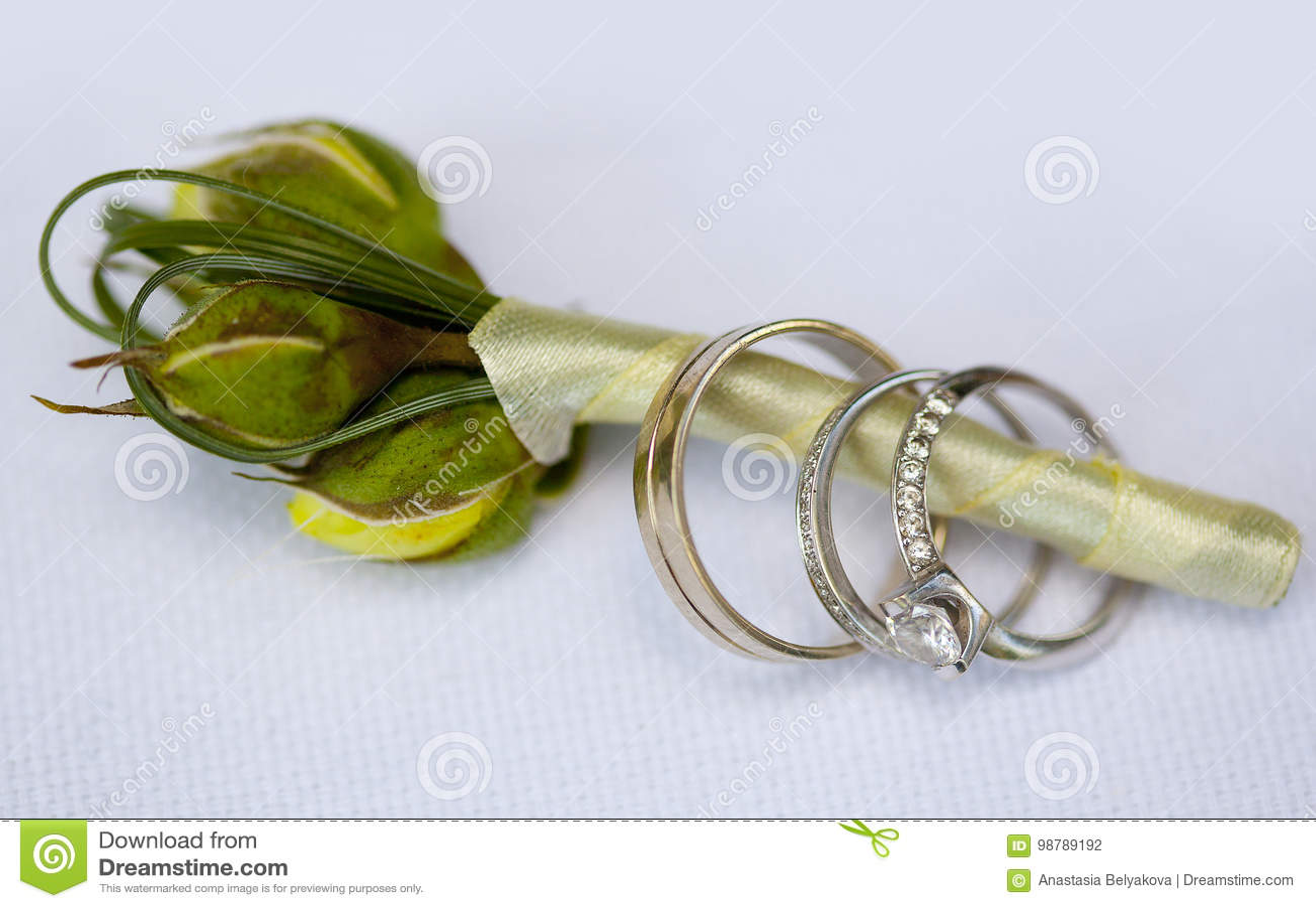 As alianças de casamento e o anel de noivado de prata com o diamante  oferecido no boutonniere do noivo com os botões de rosas amarelas e de seda  empalidecem ... bce75f21d2a4e