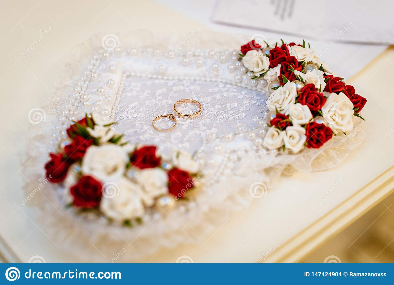 Alianças de casamento em um descanso coração-dado forma com flores