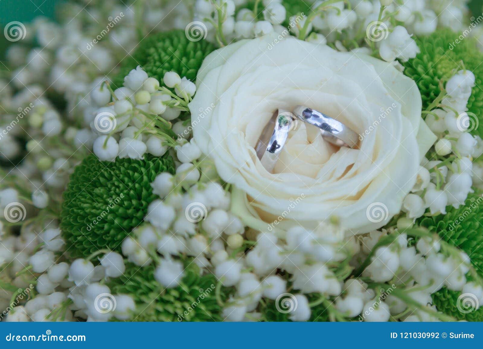 Alianças de casamento no fundo das flores