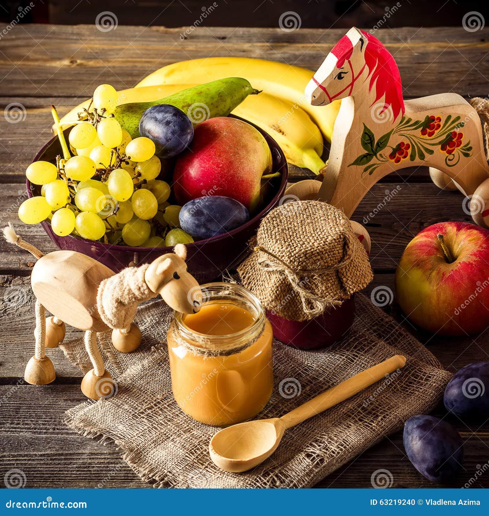 Aliment pour bébé, fruits et jouet sur la table en bois
