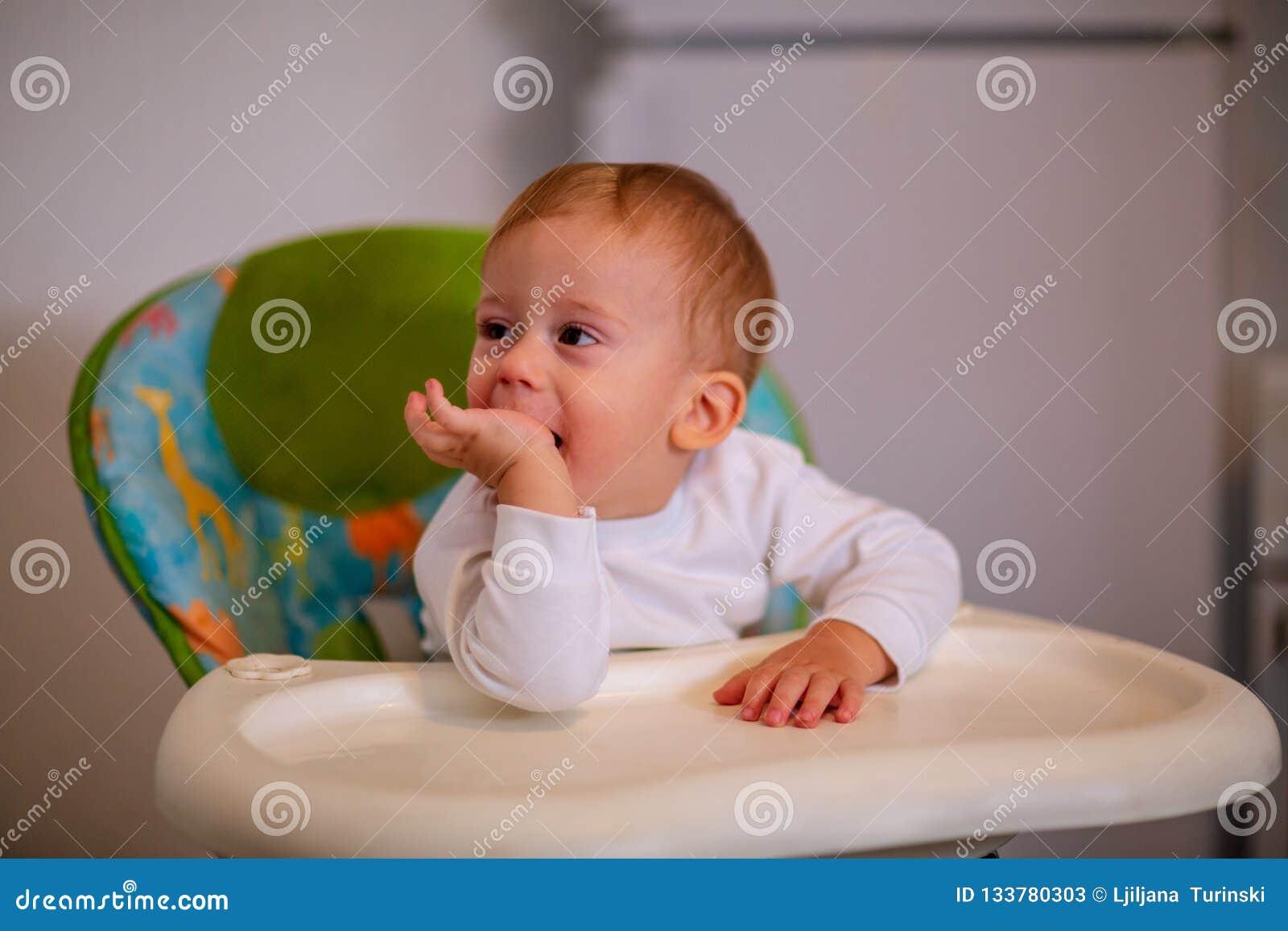Alimentación infantil muchacho alegre que se sienta en el highchair