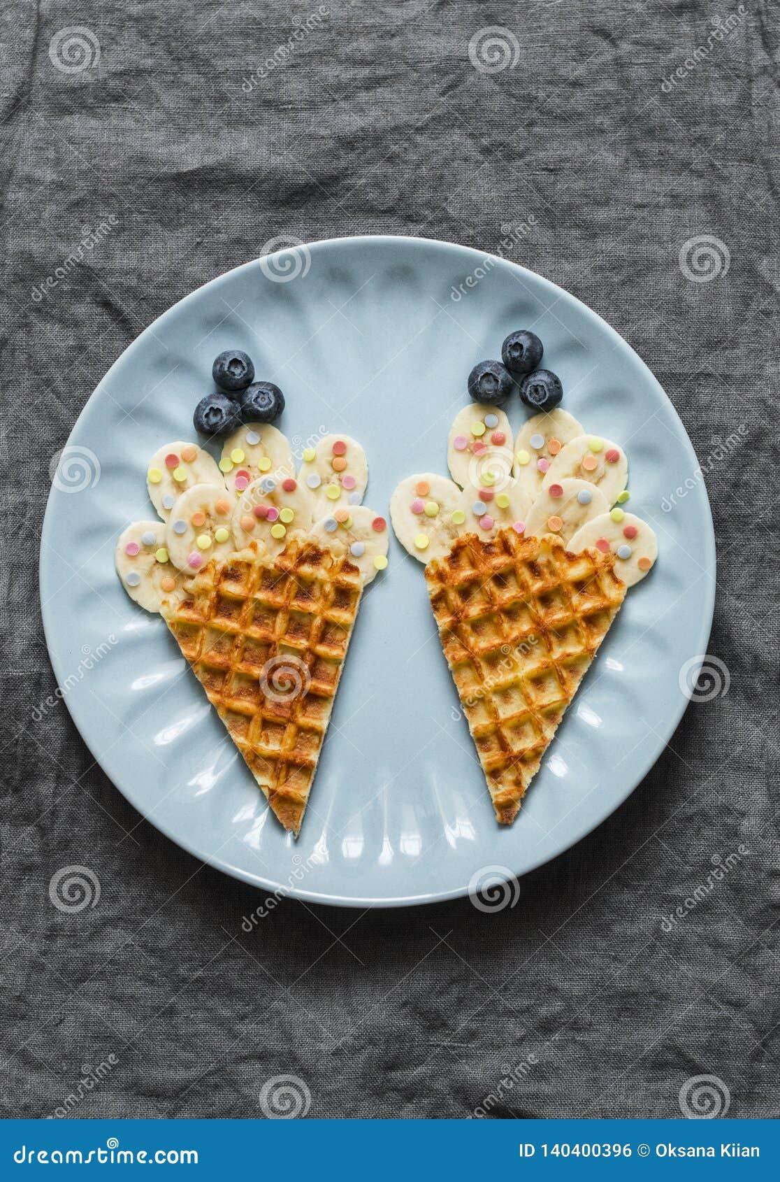 Alimenti per bambini creativi di divertimento Cialde con la banana ed i mirtilli su un fondo grigio, vista superiore L alimento a