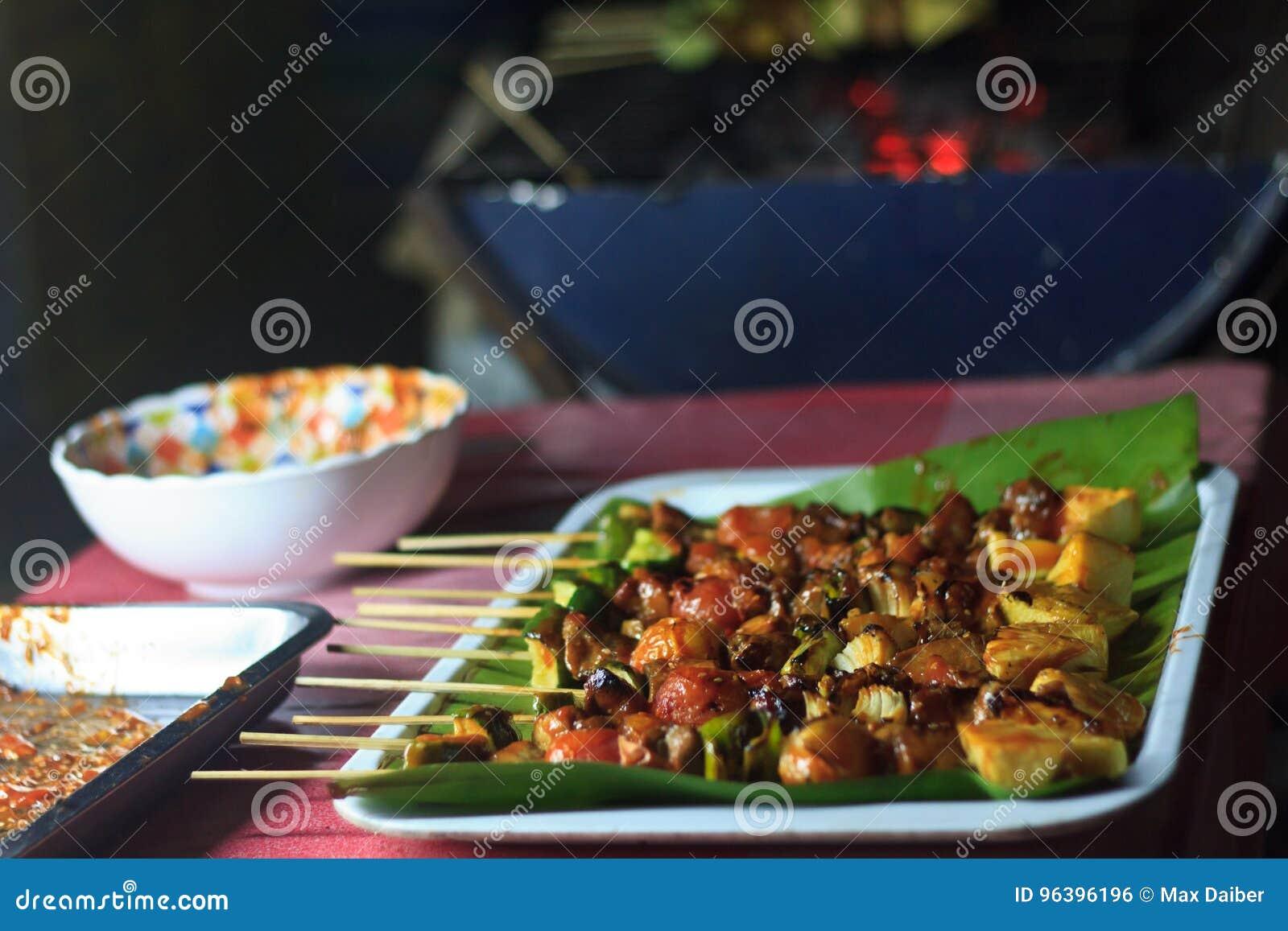Alimento asiático tradicional no mercado Carne grelhada picante deliciosa da galinha em varas