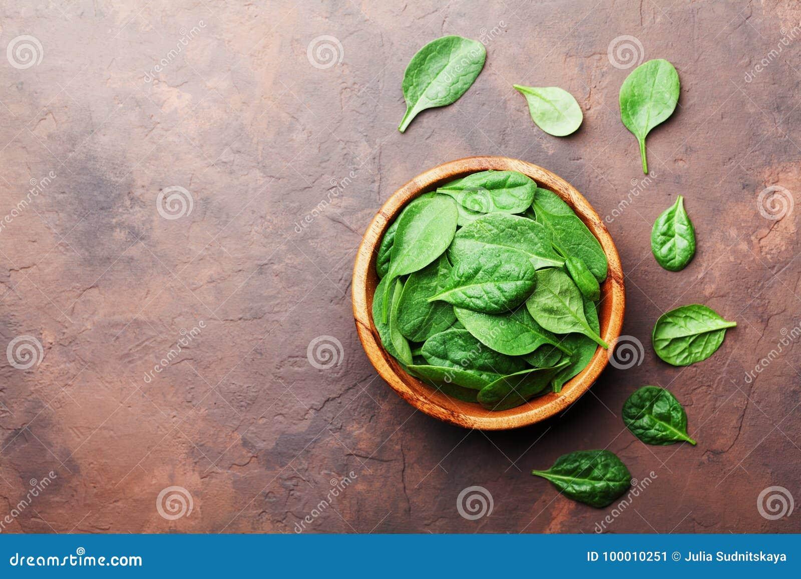 Alimento biológico La espinaca del bebé se va en cuenco de madera en la opinión de sobremesa de piedra rústica Copie el espacio p