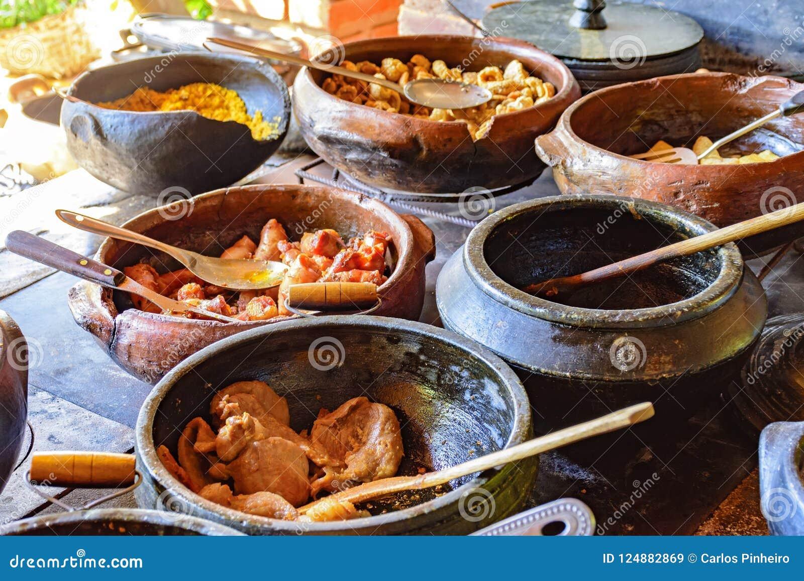 Alimento brasileiro tradicional que está sendo preparado em uns potenciômetros de argila
