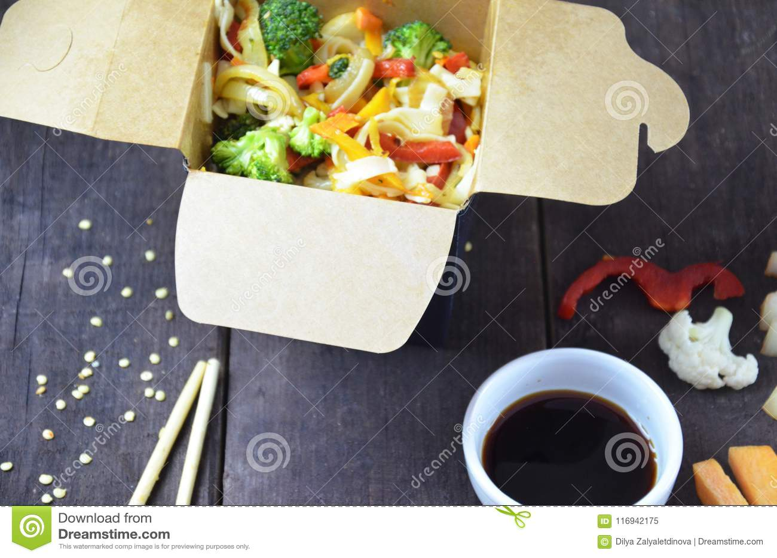 Alimento chinês, macarronetes com carne de porco e vegetais na caixa para viagem na tabela de madeira