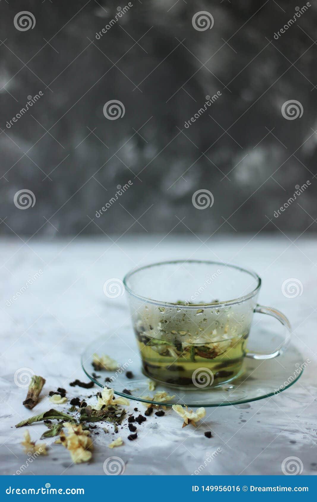 Alimento da desintoxicação e para beber o conceito healfhy do estilo de vida Copo de vidro do chá verde com jasmim em um fundo ci