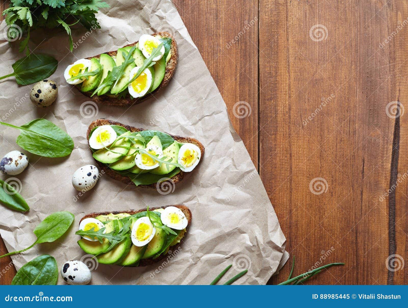 Alimento da mola Um sanduíche inteiro do brinde do pão da grão com os ovos do abacate, dos espinafres, do guacamole e de codorniz