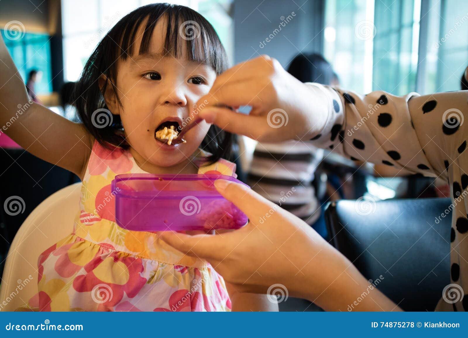 Alimento de alimentação da filha da criança da mãe asiática