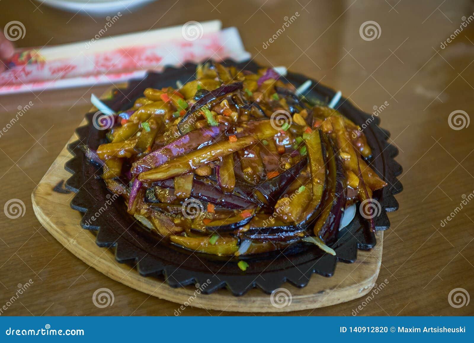 Alimento de China Beringelas com alho e cenoura sob o sause na placa escura