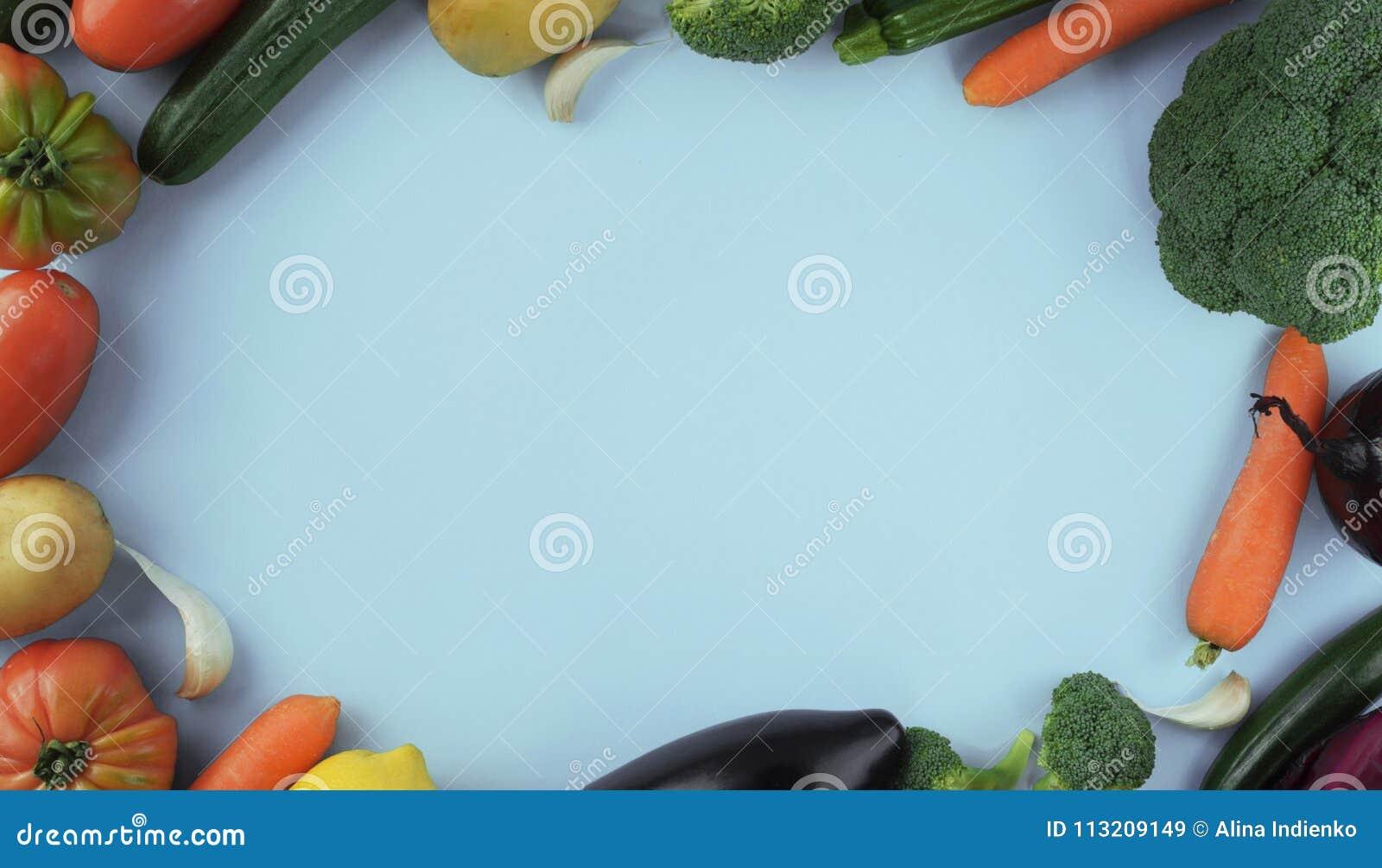 Alimento e pratos do vegetariano Vegetal no fundo azul com sp da cópia