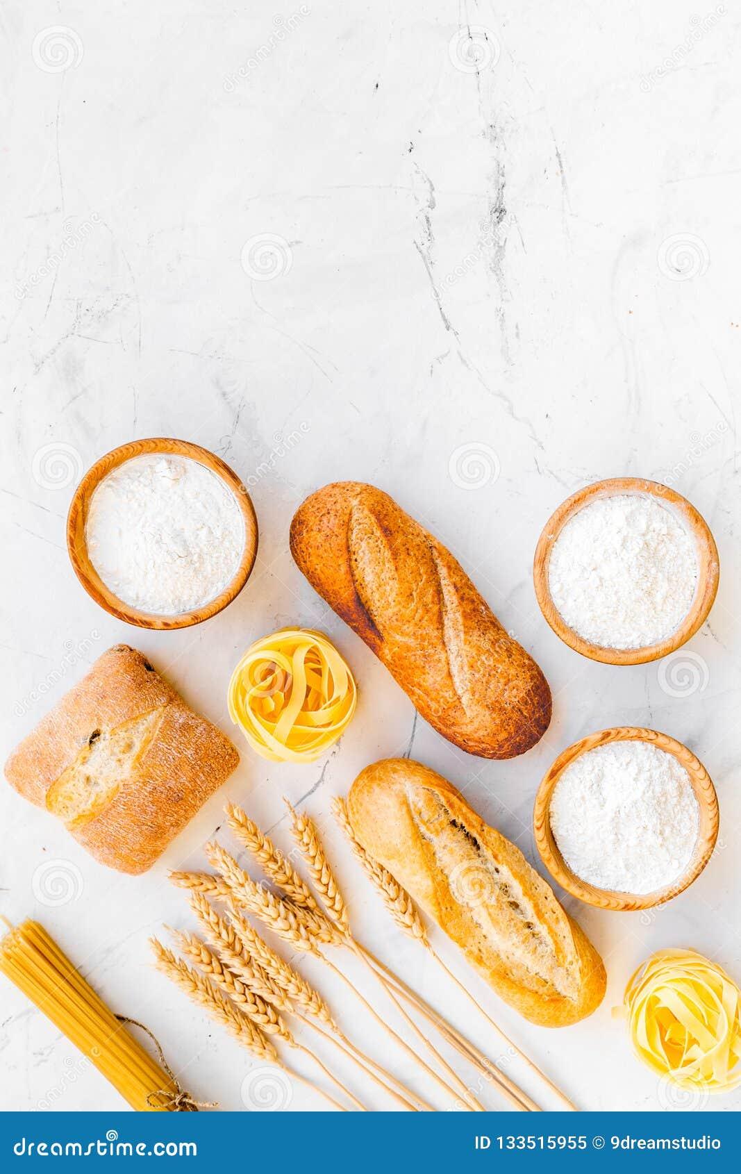 Alimento farinoso Pane fresco e pasta cruda vicino a farina in orecchie del grano e della ciotola sulla copia bianca di vista sup