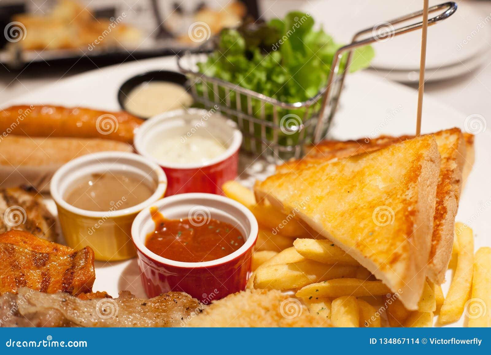 Alimento focalizado seletivo, batatas fritas e bifes do pão da manteiga e variedade tomando partido cozidos das salsichas com var