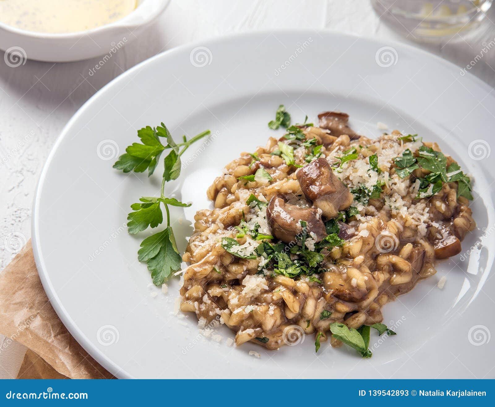 Alimento italiano Risotto con las setas y el queso en una placa blanca en un fondo blanco