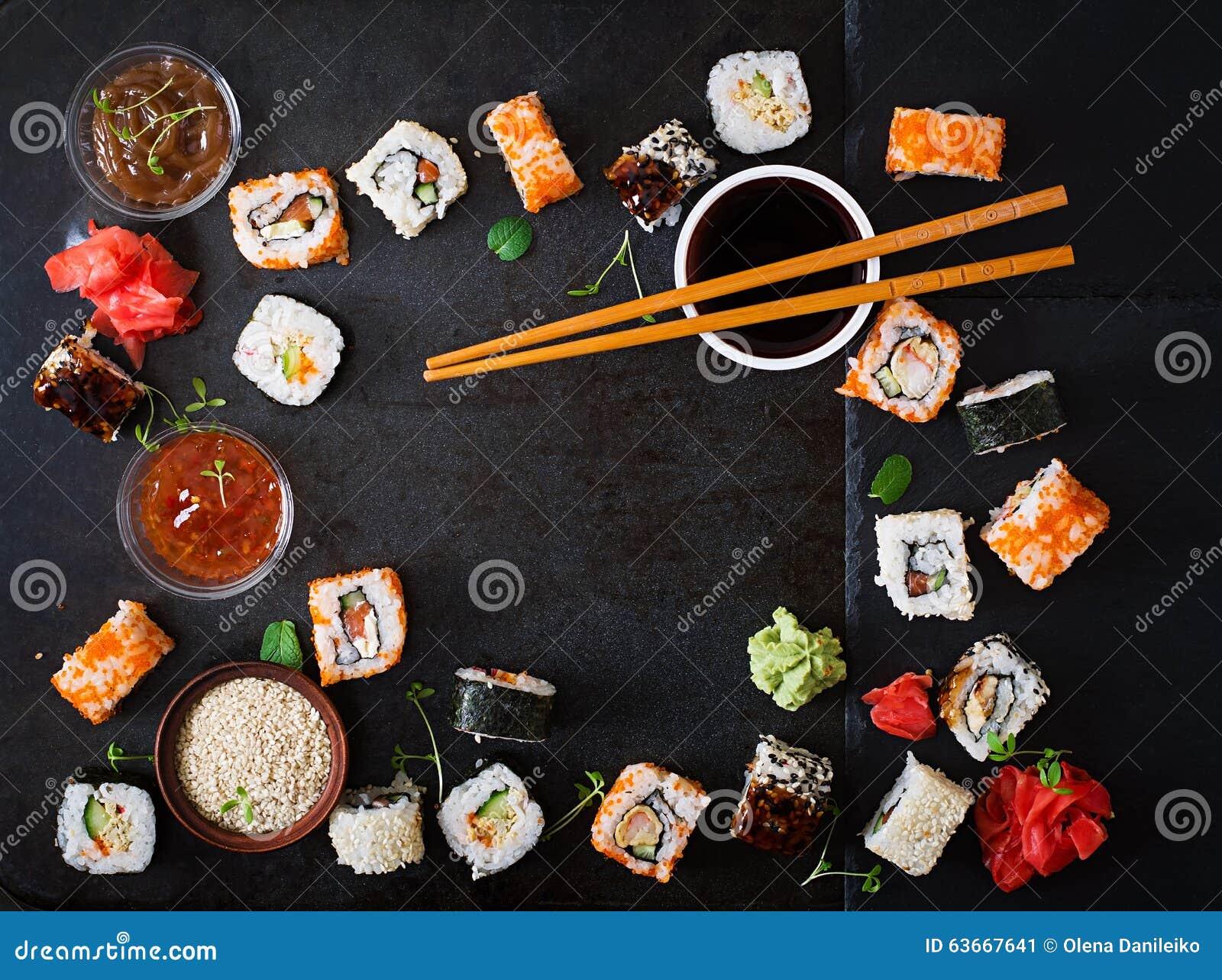 Alimento japonês tradicional - sushi, rolos e molho em um fundo escuro