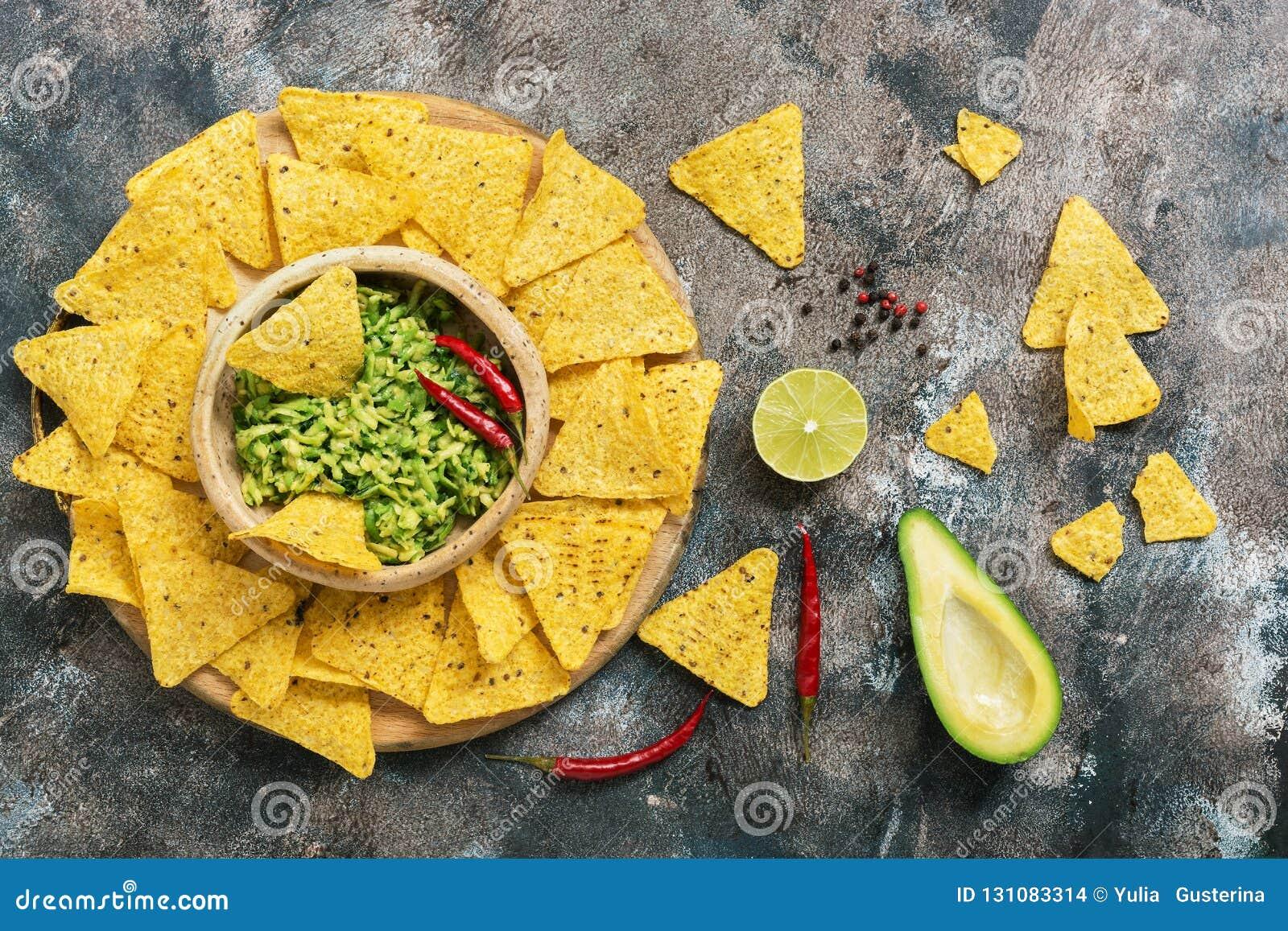 Alimento, nachos e molho mexicanos tradicionais do guacamole no fundo rústico Vista superior, configuração lisa
