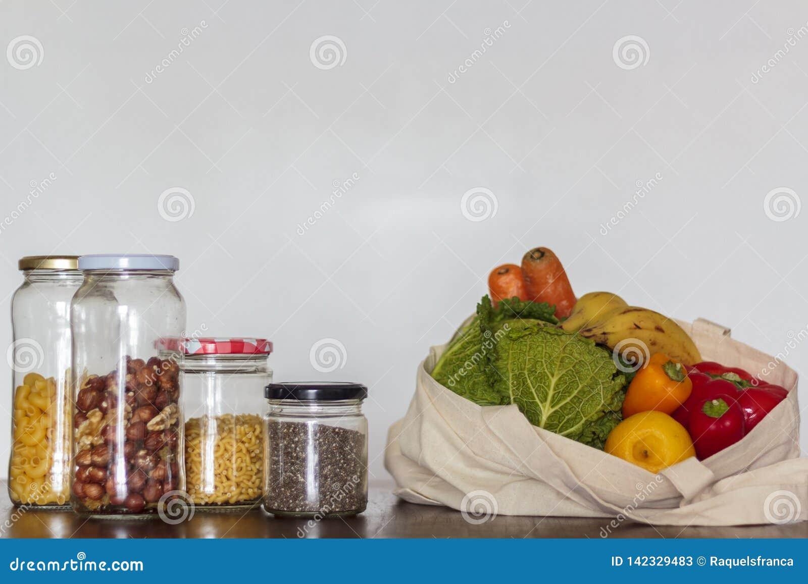 Alimento nos frascos de vidro e saco reusável com mantimentos Desperdício zero, conceito livre plástico