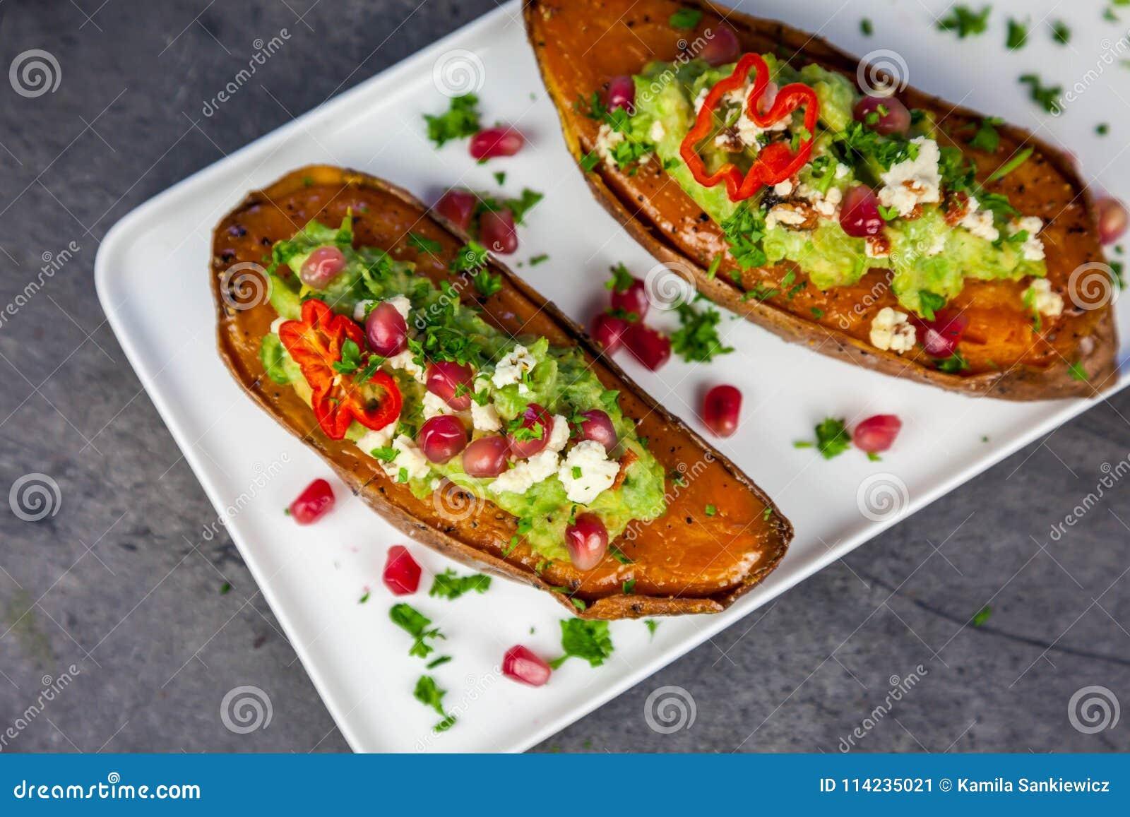 Alimento sano - le patate dolci al forno sono servito con guacamole, feta ed il melograno